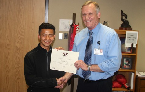 Cristian Garay, 10, receives the President's Volunteer Service award from Principal Hughes Wednesday , March 2.