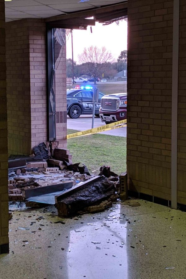 The broken window site where the black Cadillac hit the building.