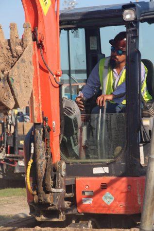 A worker preparing the baseball turf.